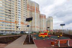 Le terrain de jeu des enfants dans la cour d'une maison de rapport avec les panneaux solaires Image stock