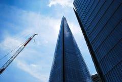 Le tesson plus une grue et un immeuble de bureaux vitreux différent Photographie stock libre de droits