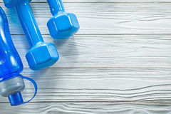 Le teste di legno blu della bottiglia di acqua sul bordo di legno mette in mostra il concep di addestramento Fotografia Stock