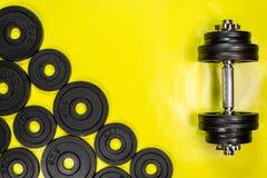 Le teste di legno della palestra con i pesi neri 1kg e 2kg del metallo su fondo giallo con il sapce della copia, fotografano pres fotografie stock libere da diritti