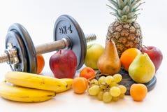 Le teste di legno ed i frutti assortiti e la misura legano il concetto con un nastro sano di perdita di peso di stile di vita Fotografia Stock
