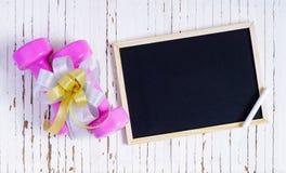 Le teste di legno ed il regalo rosa di sport si piegano con la lavagna ed il gesso su w Immagine Stock