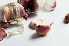 Le teste ed i chiodi di garofano dell'aglio su marmo bianco sorgono fotografia stock