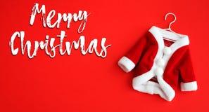 Le texte blanc de Joyeux Noël et manteau de Santa Claus Saint Nicholas le mini adaptent au costume avec le fond d'isolement par m photo stock