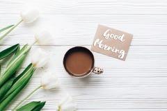 Le texte bonjour se connectent la carte de voeux aux tulipes avec du café dessus Image stock