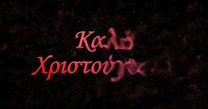 Le texte de Joyeux Noël dans le Grec se tourne vers la poussière de la droite sur le noir Photos stock