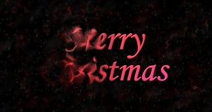 Le texte de Joyeux Noël se tourne vers la poussière de la gauche sur le fond noir Image stock