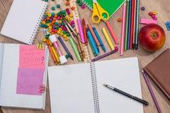 Le texte de nouveau à l'école écrivent le bloc-notes avec différentes fournitures scolaires Images libres de droits