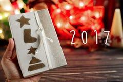 le texte de 2017 signes en main tenant Noël a enveloppé la boîte actuelle dessus Images libres de droits