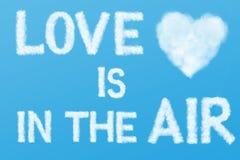 Le texte et le coeur opacifient dans le ciel bleu Image libre de droits