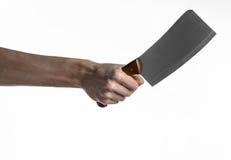 Le thème de la cuisine : Main de chef jugeant un grand couteau de cuisine pour couper la viande sur un fond blanc d'isolement Photos libres de droits