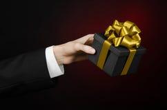 Le thème des célébrations et des cadeaux : un homme dans un costume noir jugeant un cadeau exclusif emballé dans une boîte noire  Photos libres de droits