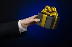 Le thème des célébrations et des cadeaux : un homme dans un costume noir jugeant un cadeau exclusif emballé dans une boîte noire  Photo stock