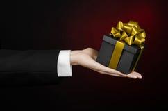 Le thème des célébrations et des cadeaux : un homme dans un costume noir jugeant un cadeau exclusif emballé dans une boîte noire  Image libre de droits