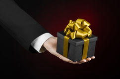 Le thème des célébrations et des cadeaux : un homme dans un costume noir jugeant un cadeau exclusif emballé dans une boîte noire  Image stock