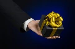 Le thème des célébrations et des cadeaux : un homme dans un costume noir jugeant un cadeau exclusif emballé dans une boîte noire  Photographie stock libre de droits