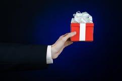 Le thème des célébrations et des cadeaux : un homme dans un costume noir jugeant un cadeau exclusif enveloppé dans la boîte rouge Photos stock