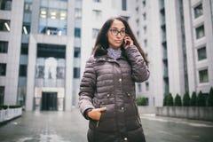 Le thème est la conjoncture économique Belle jeune femme d'appartenance ethnique européenne avec les verres de port et le manteau image stock