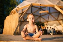Le thème est yoga et des enfants Enfant caucasien de garçon se reposant nu-pieds en tailleur en position de lotus sur le plancher Photographie stock libre de droits