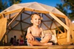 Le thème est yoga et des enfants Enfant caucasien de garçon se reposant nu-pieds en tailleur en position de lotus sur le plancher Photos libres de droits