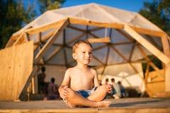 Le thème est yoga et des enfants Enfant caucasien de garçon se reposant nu-pieds en tailleur en position de lotus sur le plancher Image libre de droits
