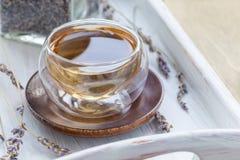 Le thé de fines herbes sain de lavande dans la tasse en verre avec la lavande fleurit sur le fond, horizontal Image stock