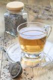 Le thé de fines herbes sain de lavande dans la tasse en verre avec la lavande fleurit sur le fond, vertical Photos libres de droits