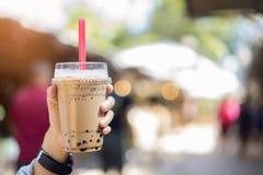 Le thé de lait de bulle en verre chez les femmes remettent image stock