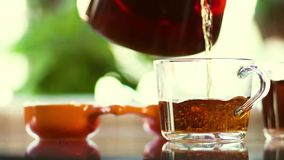 Le thé frais aromatique chaud est versé dans une tasse en verre clips vidéos