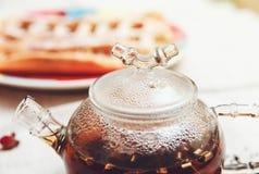 Le thé noir dans la théière en verre, avec la transpiration ; Thé buvant, fleurs aromatisées, modifiées la tonalité Images libres de droits