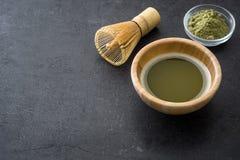 Le thé vert de Matcha dans une cuvette et le bambou battent sur l'ardoise photos stock