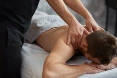 Le thérapeute professionnel de massage soigne un patient masculin en appartement image stock