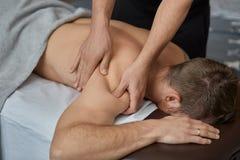 Le thérapeute professionnel de massage soigne un patient masculin en appartement photographie stock
