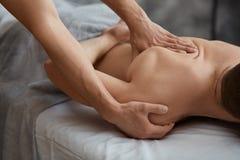 Le thérapeute professionnel de massage soigne un patient masculin en appartement images stock