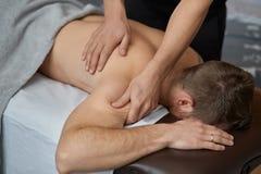 Le thérapeute professionnel de massage soigne un patient masculin en appartement photo libre de droits