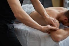 Le thérapeute professionnel de massage soigne un patient masculin en appartement photo stock