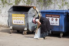 Le thésauriseur plus âgé de dame met les bouteilles à bière vides dans un sac Images libres de droits