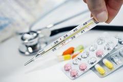 Le thermomètre en verre médical dans les mains de la température sur le fond de diverses drogues, les vitamines, les antibiotique photo libre de droits