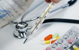 Le thermomètre en verre médical dans les mains de la température sur le fond de diverses drogues, les vitamines, les antibiotique photographie stock libre de droits