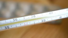 Le thermomètre mercuriel en verre prend la température banque de vidéos