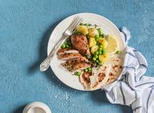 Le thym de citron a fait le poulet, les pommes de terre et les pois cuire au four d'un plat blanc sur un fond bleu Image libre de droits