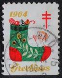 Le timbre de Noël imprimé aux Etats-Unis montre un bas avec des cadeaux photo stock