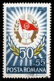 Le timbre imprimé en expositions de la Roumanie Badge et guirlande de laurier, 50 ans de ligue de la jeunesse communiste Images libres de droits