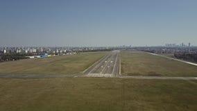 Le tir aérien d'un aéroport de ville a plaqué la piste un jour ensoleillé Photo libre de droits