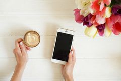 Le tir aérien de la femme remet tenir l'art de latte de cappuccino de la tasse W d'instrument et de café de téléphone portable su image libre de droits