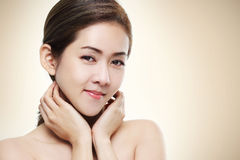 Le tir asiatique de beauté de femmes lui montrent des bonnes santés de visage sur le fond chaud d'or de couleur Photo libre de droits