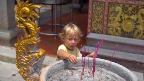 Le tir au ralenti d'un petit garçon dans un temple bouddhiste met un bâton aromatique dans un encensoir banque de vidéos