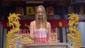 Le tir au ralenti d'une jeune femme dans un temple bouddhiste met un encensoir aromatique de bâton banque de vidéos