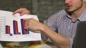 Le tir cultivé d'une apparence d'homme d'affaires a imprimé des diagrammes sur une réunion d'affaires photo stock