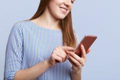 Le tir cultivé de la jeune femelle avec l'expression gaie tient le téléphone portable moderne, messages avec des amis, reliés à l Images libres de droits